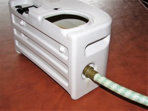Dehumidifier water collection tank with hose attached to side